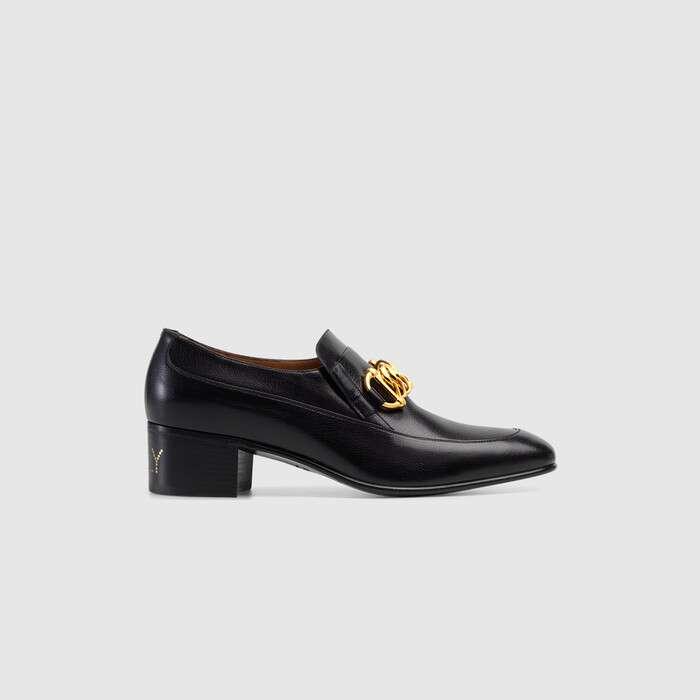 """以现代时尚风格演绎源自 18 世纪和 19 世纪的经典男鞋系列,该系列乐福鞋饰有马衔扣细节的粗犷金色调链条和贵金属 G 搭扣。每一季,亚力山卓·米开理都会从英国德文郡第 11 世公爵 Andrew Cavendish 和查茨沃斯庄园汲取灵感,本季最新系列也不例外,在他为自己和客人提出的 22 条颇具讽刺意味的口号基础上,推出全新的格言警句。这一男款黑色皮革乐福鞋的写跟上饰有排列成""""Ice Lolly""""字样的饰钉细节"""